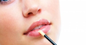 Stock-photo-of-woman-applying-lipgloss