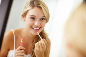 Young-woman-applying-lip-gloss