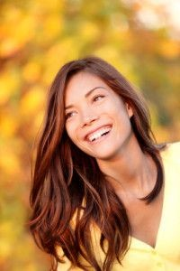 Fall woman smiling - Autumn portrait of happy lovely and beautiful mixed race Asian Caucasian young woman in forest in fall colors.